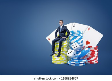 A tiny businessman sits on a stack of casino chips near large dice and playing cards. Casino games. Gambling for big money. Waiting for huge prize.