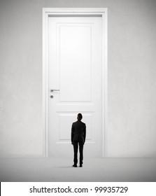 Tiny businessman standing in front of a giant door