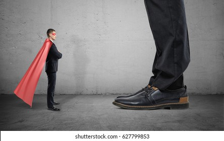 A tiny businessman in a superhero cape stands facing giant man with only his feet seen. Business competitors. Small and big companies. Monopolistic market.