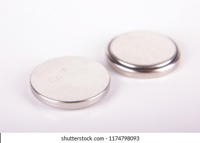 Tiny button cell CR2032 batteries both sides isolated on the white background