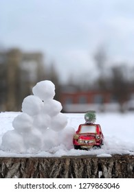 tiny car toy with christmas tree. christmas preparation concert. red car in the snow