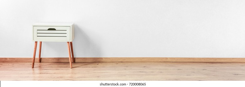 Tiny chest of drawers standing in a clean, empty white room with a wooden floor
