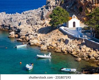 Tiny church and boats at St Pauls Bay Lindos Rhodes Greece Europe