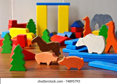 Tiny colorful wooden toy shapes and building blocks on hardwood floor.  Macro with extremely shallow dof.  Selective focus on toys in foreground.
