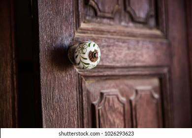 A tiny doorknob is colored in contrast to the brown wooden door it opens.