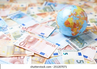 Tiny Earth globe over the surface covered with the multiple bank note bills