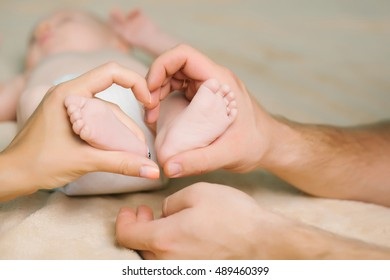 Tiny feet with cute heel of newborn baby in mother and father hands forming heart shape on light background closeup