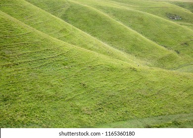 A tiny figure in the distance dwarfed by the steep face of the Chiltern Hills at The Vale of the White Horse in Oxfordshire UK. Bright green grass on a steep slope with a walker at the bottom.