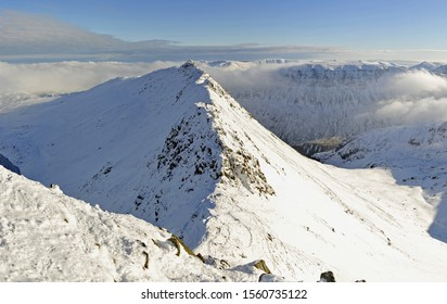 The tiny figure of a lone climber on Striding Edge leading to Helvellyn on a clear day, with perfect conditions for winter climbing. An air of solitude & tranquility prevails.