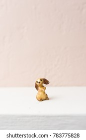 Tiny figurine of a begging dog on white shelf with pink background