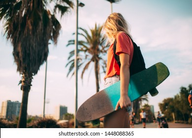 Tiny fit hipster girl skating on the seaside during amazing sunset sometimes using mobile phone