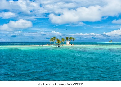 Tiny island with coconut trees and boat in Belize