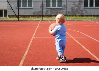tiny little boy playing with a basketball