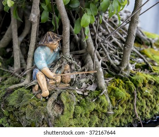 Tiny model of  a fisherman beneath a bonsai fig tree  outside Ngoc Son Temple, Hanoi, Vietnam