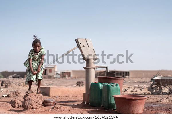 Tiny Native African Schoolgirl Bringing Tap Water in an arid zone