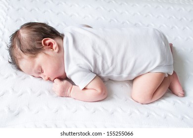 Tiny newborn baby sleeping on a white knitted blanket