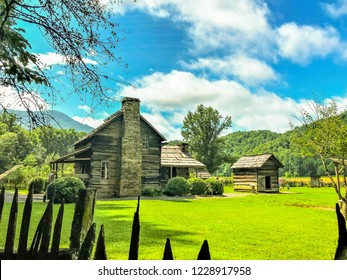 A tiny old vintage wooden house on the beautiful environment of green grass, mountain and white cumulus clouds with clear blue sky is on the background, Summer in North Carolina USA