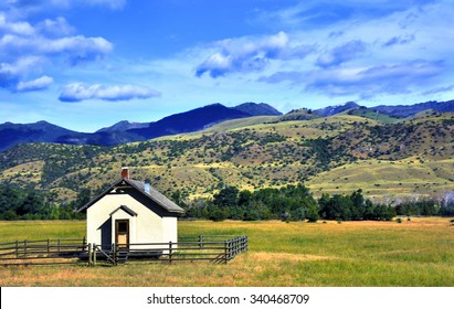 Tiny one room school house sits on the valley floor in Paradise Valley.  Wooden fence surrounds school and Gallatin Mountains rise in the back.