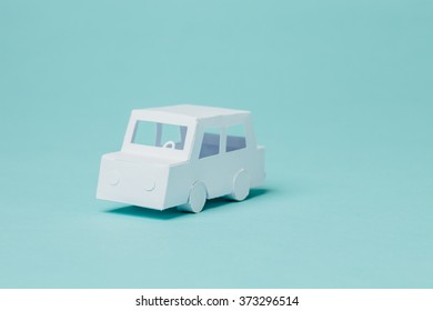 Tiny paper car on blue background.