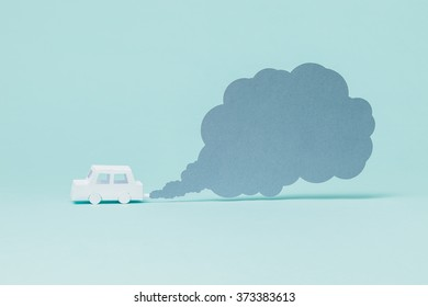 Tiny paper car and smoke on blue background.