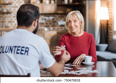 Tiny piece. Cheerful smiling senior woman looking glad while sitting at the table with a young volunteer and a holding a piece of puzzle in her hands