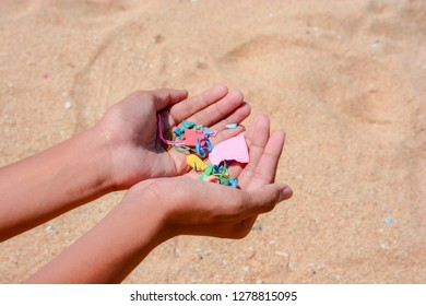 Tiny pieces of plastic collected from sandy beach in hands of environmentalist. Microplastic is polluting the sea and marine ecosystem.