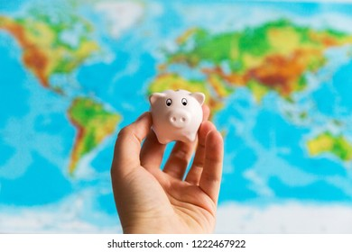 A tiny piggy bank is held in the hand. A colorful map of the world in the background. Travel concept. Collecting money for the holidays