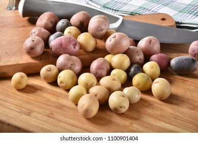 Tiny red, purple and yukon gold potatoes on a cutting board with a knife.