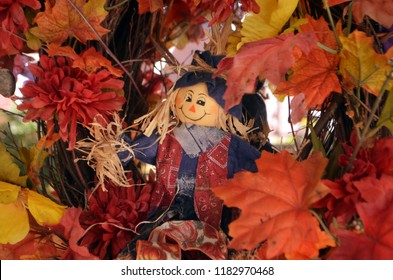 tiny smiling scarecrow in the middle of festive fall wreathe arrangement