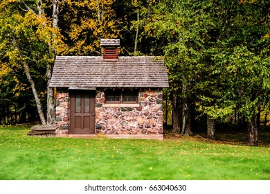 Tiny Stone House. Side view of a tiny stone house with autumn foliage in the yard. This is a historical structure in a national forest and not private property.