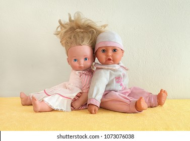 Tiny tots dolls in pink clothes. Nursery dolls sitting back to back on yellow underlay next to the wall. Caucasian newborn baby puppets. Studio shot. Pair of figureheads sitting behind another.