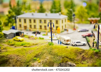 Tiny toy people figures on grass near house on miniature layout landscape
