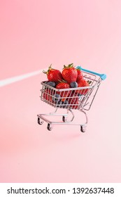 Tiny toy shopping cart holding strawberries and blueberries is standing on one wheel. Conceptual studio shot representing shopping for seasonal fruit products.