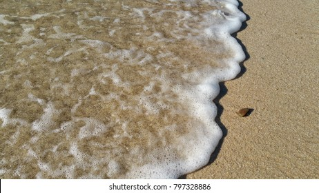 Tiny waves on the wet sand/ beach