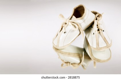 Tiny white baby booties reflected on background