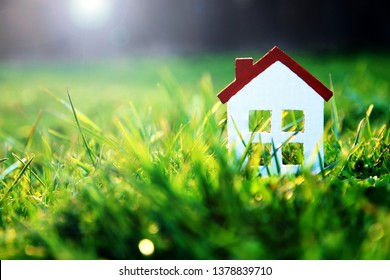 Tiny white toy house with red brick roof in bright green grass in sunlight