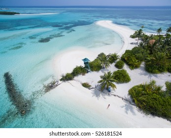 Tiny woman lying down at the white sandy beach with lifeguard tower seen from above. Landscape seascape aerial view over a Maldives Male Atoll island.