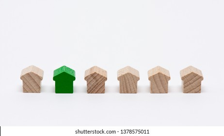 Tiny wooden toy houses in a row, one of them painted green, white background
