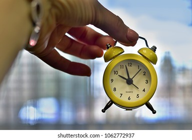 tiny yellow alarm clock hanging on the fingers showing that it is already time