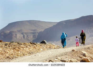 Tinzouline, Morocco - February 27, 2016:The back of 3 nomad women in traditional dress walking in the deserts of Tinzouline, Morocco.