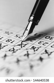 Tip of fountain pen marking date in calendar (b&w) (close-up)