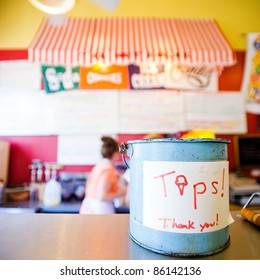 Tip jar in a colorful ice cream shop.
