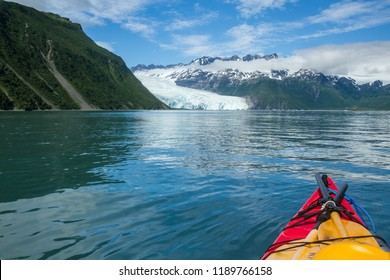 Tip of a kayak in water in front of Aialik Glacier, Aialik Bay, Alaska, USA. Kayak in foreground, water in mid-ground, glacier and blue sky in background.