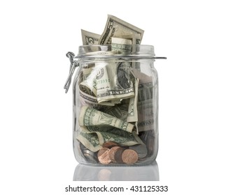 A tip or savings jar filled over the top with American coins and bills.