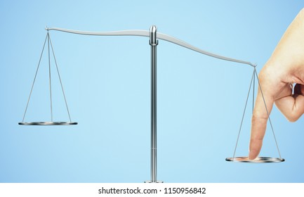 Tip the scales of justice concept. Finger illegaly influencing the legal system for an unfair advantage on blue backdrop.