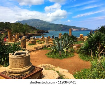 Tipaza, Algeria - May 7, 2016: Visitors are wolking among the ancient columns of archaeological Roman site near by Mediterranean Sea.