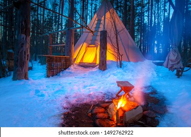 Tipi in winter forest. National Indian house. Nomadic lifestyle. The Lodge is lit from the inside. Campfire in front of the tent. Eco-tourism.