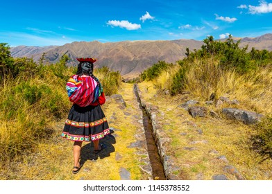 TIPON, PERU - JULY 22, 2018: Young quechua indigenous woman walking along an inca aqueduct in the archaeological site of Tipon near the city of Cusco, Sacred Valley of the Inca.