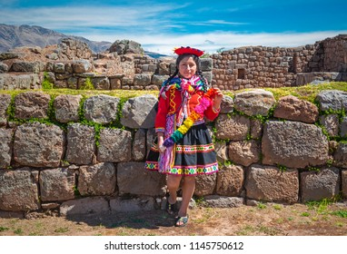 TIPON, PERU - JULY 24, 2018: Young indigenous Quechua lady in traditional clothing and hairstyle inside the Inca ruin of Tipon near Cusco city.