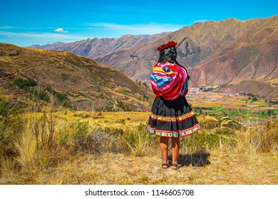 TIPON, PERU - JULY 24, 2018: Young indigenous Quechua girl looking at the Sacred Valley of the Inca in the Andes mountain range near Cusco city.